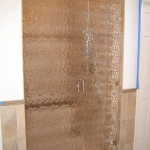 A textured glass shower door from Santa Fe Glass in Independence, MO