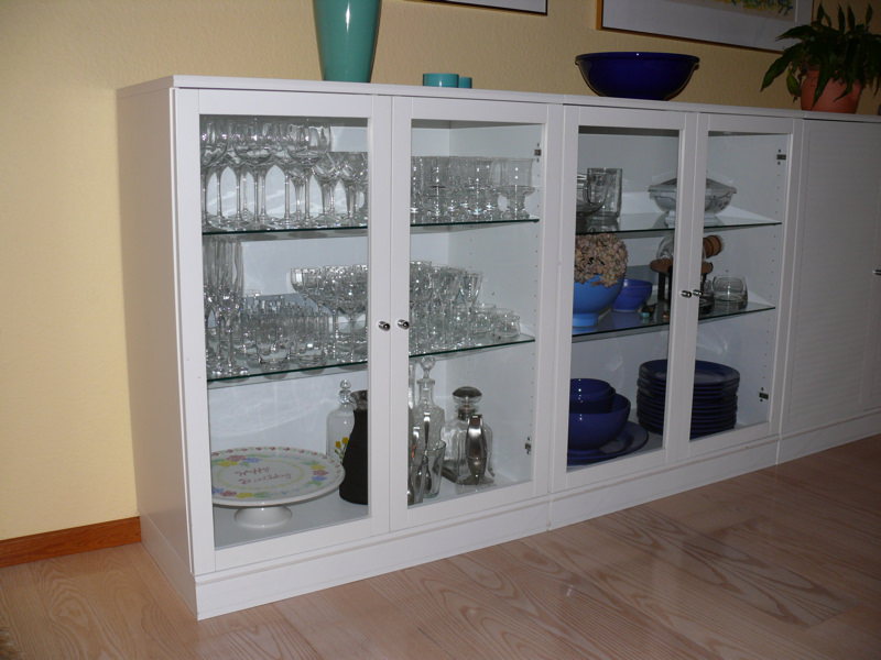 white glass cabinet filled with dinnerware